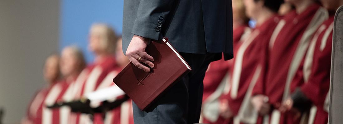 Close-up photo of Fair Haven Baptist Church Senior Pastor Andy Briggs holding a Bible by his side